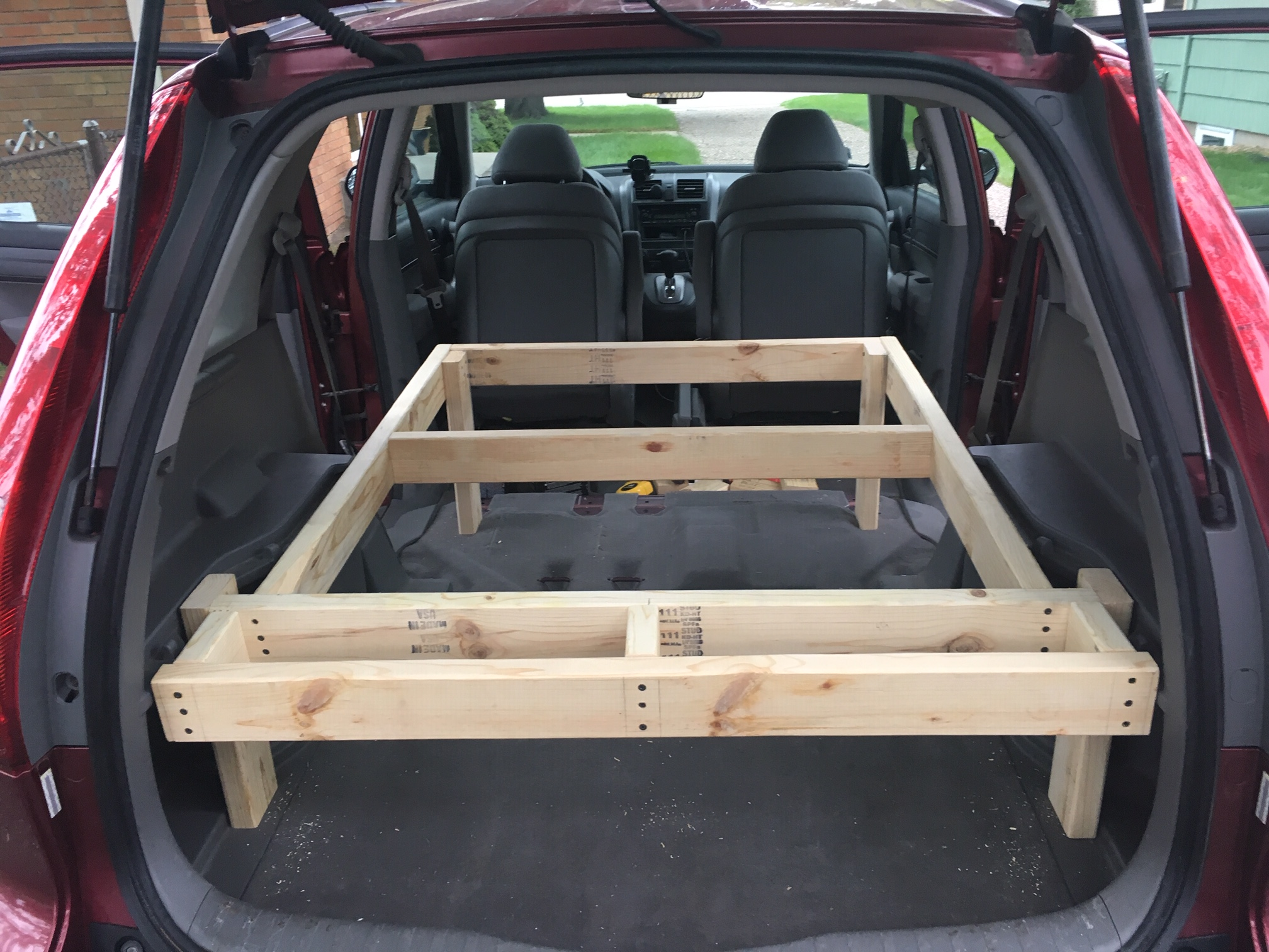 Maximizing the square footage for the sleeping platform by claiming all the available space behind the hatchback